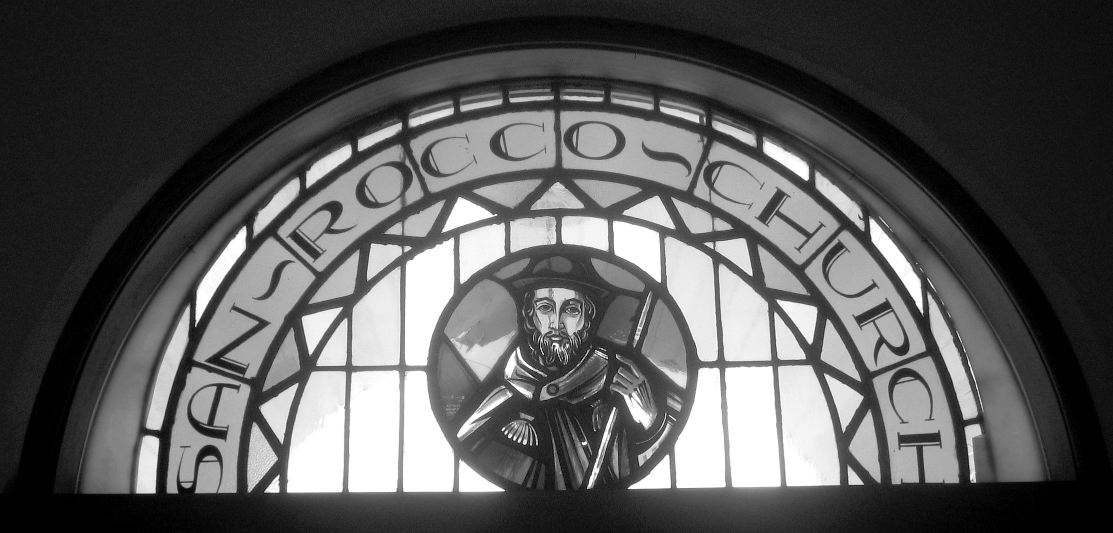 Stained Glass Window of St Rocco, above the front door of the church
