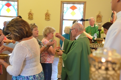 Father Petrongelli gives Communion to the people, here Karen Jacobucci.