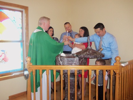 After the baptism, the parents and godparents together hold a candle, lit from the Easter candle.