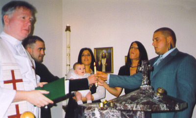 After baptism, parents and godparents hold a lit candle.