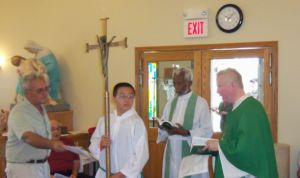 Fred LoBue, usher, left, offers a bulletin to the clergy.